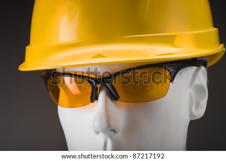 white dummy head with yellow security helmet and glasses - stock photo