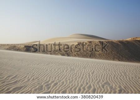 White dunes, rippled sand going far under blue sky, Vietnam - stock photo