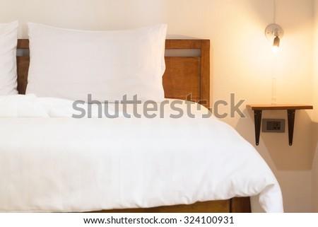 white duvet on vintage wood bed. - stock photo