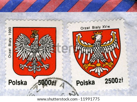 white eagle on red, national emblem of Poland, in two old (1992) canceled post stamps with air mail envelope background - modern and XV century versions