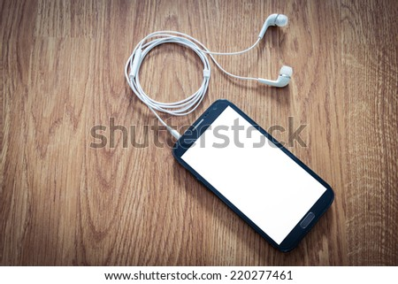 white earphones attached to smartphone on wooden background - stock photo