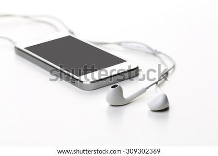 White earphones on white background - stock photo