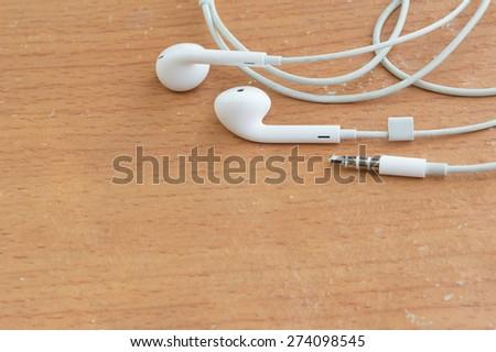 white earphones on wooden board - stock photo