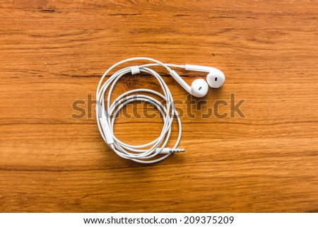 white earphones over wooden board