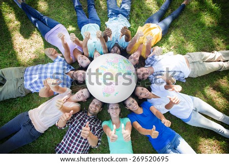 White earth with text against happy friends in the park lying in circle - stock photo