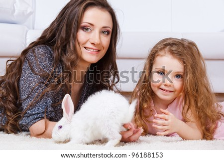 White Easter bunny beside happy mother and daughter - stock photo