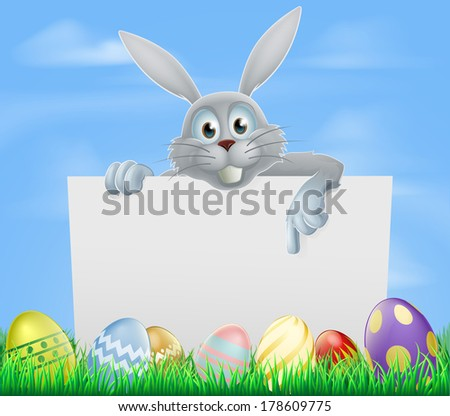 White Easter bunny peeking over a sign and pointing with Easter eggs in a spring field