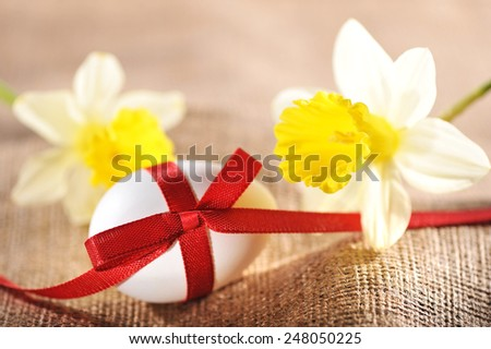 White Easter egg with red bow on jute bag with narcissus - stock photo