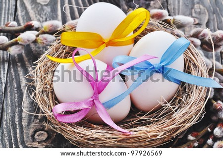 White easter eggs with color bow and willow - stock photo