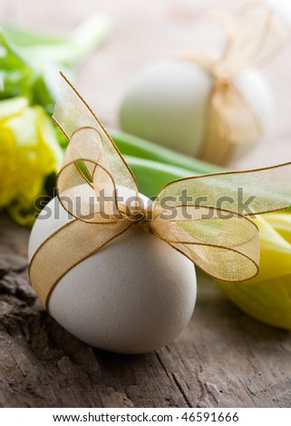 White easter eggs with golden bow and tulips