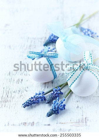 White easter eggs with ribbons and grape hyacinths - stock photo