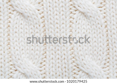 White/ecru knitted woolen fabric as a background