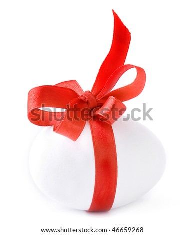White egg wrapped around with red ribbon bow over white background