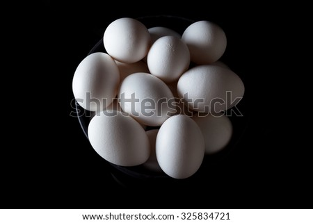 White eggs in a black bowl on black background from above