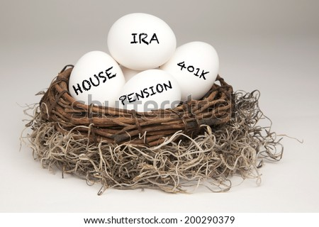White eggs in a brown nest labeled with IRA, Pension, 401k and House representing a typical nest egg. - stock photo