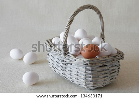 White eggs in a wattled basket on a fabric light background.