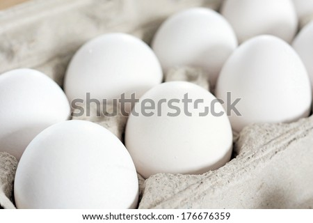 White eggs in recycled cardboard container or crate, food staple. - stock photo