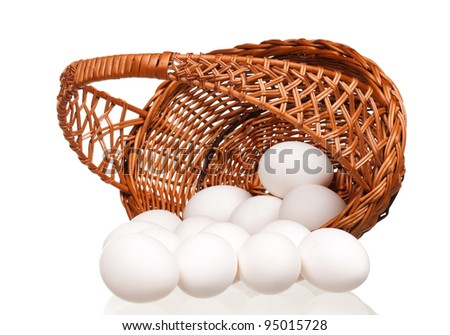 White eggs in the wicker basket over white background - stock photo