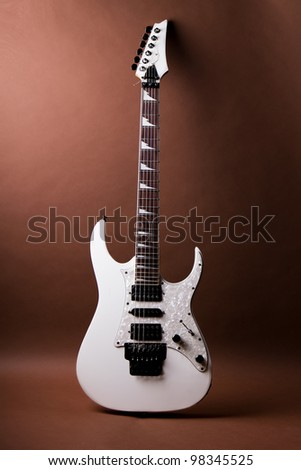 White Electric Guitar is on a brown background - stock photo