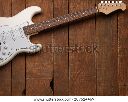 White electric guitar on a wooden vintage background with shabby