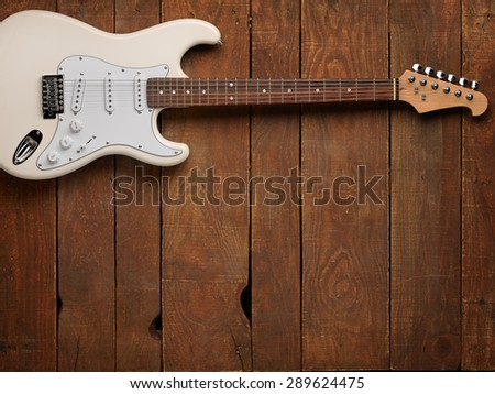 White electric guitar on a wooden vintage background with shabby - stock photo