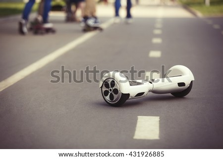 White Electric mini hover board scooter on road in park. Eco city transportation on battery power, produce no air pollution to atmosphere - stock photo