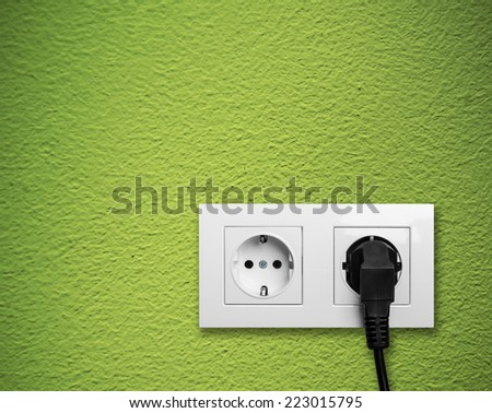 white electric outlet mounted on green wall - stock photo