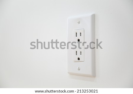 White Electrical Outlet and Wall Plate at the white wall - stock photo