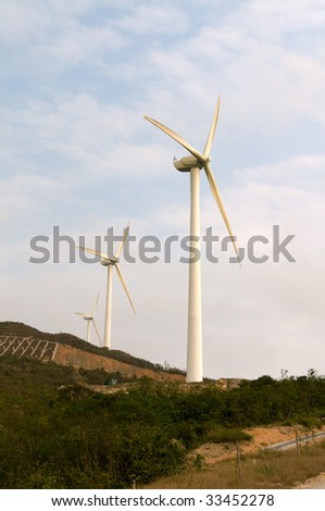 White electrical power generating wind turbines on rolling hills