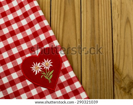 White embroidered Edelweiss flower on heart appliques on the checkered red white tablecloth on wooden table rustic background. Focus on the Edelweiss  - stock photo