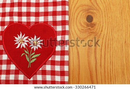 White embroidered Edelweiss  on red heart on plaid linen fabric checkered tablecloth and wooden background - stock photo