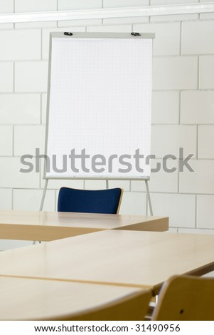 White empty billboard in a meeting room with tables and chairs - stock photo