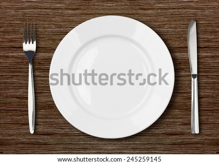 white empty dinner plate setting on dark wooden table