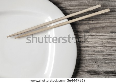White empty dish and chopsticks for sushi on the wooden table