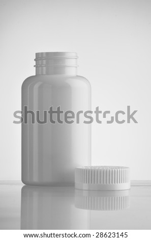 White empty medicine bottle standing with the cap at side