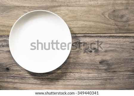 white Empty plate on old wooden background. Top view with copy space - stock photo