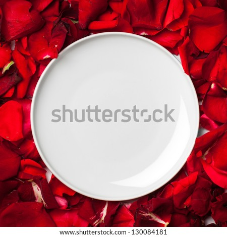 White empty plate on rose petals - stock photo