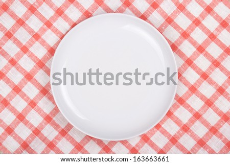 white empty plate over checkered background