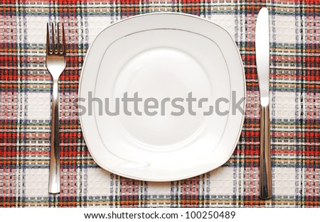 White empty plate with fork and knife on checkered tablecloth - stock photo