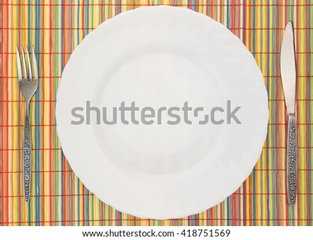 White empty plate with fork and knife on colorful bamboo placemat - stock photo