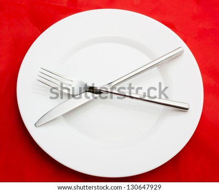 White empty plate with fork and knife on red - stock photo