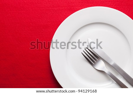 White empty plate with fork and knife on red tablecloth - stock photo