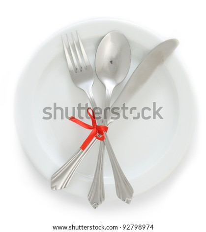 White empty plate with silver fork and spoon, knife tied with a red ribbon isolated on white - stock photo