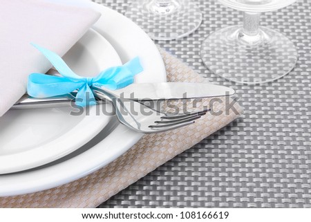 White empty plates, fork and knife tied with a ribbon and glasses on a grey tablecloth - stock photo