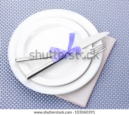 White empty plates with fork and knife tied with a ribbon on a grey tablecloth