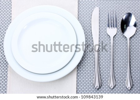 White empty plates with fork, spoon and knife on a grey tablecloth - stock photo