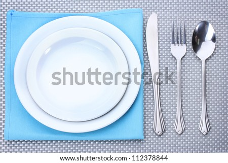 White empty plates with fork, spoon and knife on a grey tablecloth