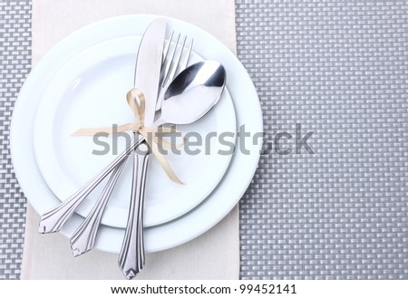 White empty plates with fork, spoon and knife tied with a ribbon on a grey tablecloth