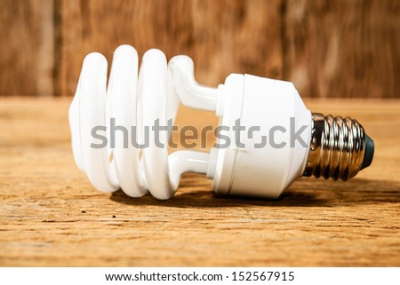 white energy saving bulb, Illuminated light bulb, CFL bulb, Realistic photo image on wood background - stock photo