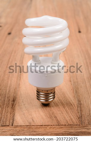 white energy saving bulb, Illuminated light bulb, Realistic photo image on wood background - stock photo
